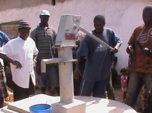 Demonstrating correct pumping techniques at the new Batkanu well